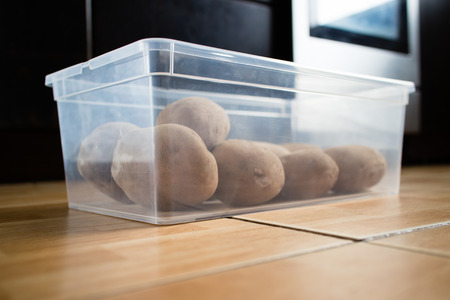 Raw potatoes in a plastic container on a kitchen floor. Stock Photo