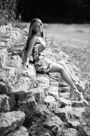 Caucasian long hair model in dress sitting on rocks. Black&white picture.