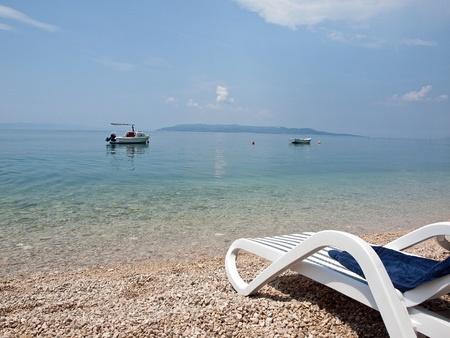 Deck chair with towel on beach with view to the island Hvar and blue sea