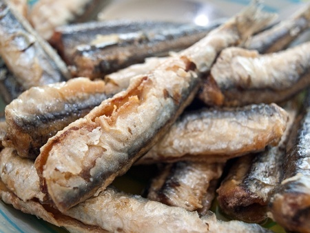 Fried anchovies on plate close up