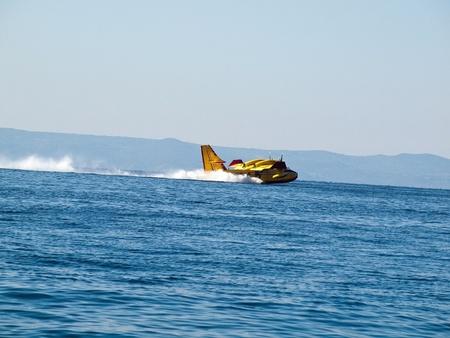 Yellow airplane landing at sea Stock Photo