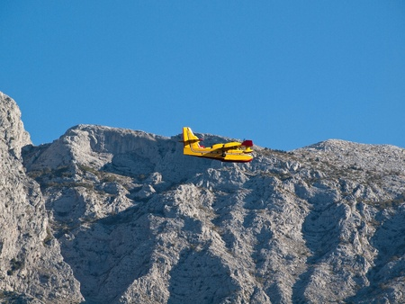 fire fighter: Fire fighter airplane flying near big mountain Stock Photo