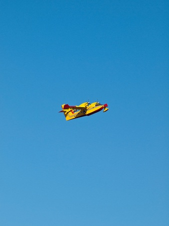 fire fighter: Yellow fire fighter airplane on blue sky background