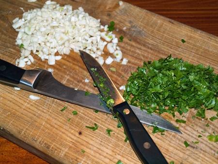 Chopped parsley and garlic on chopping board