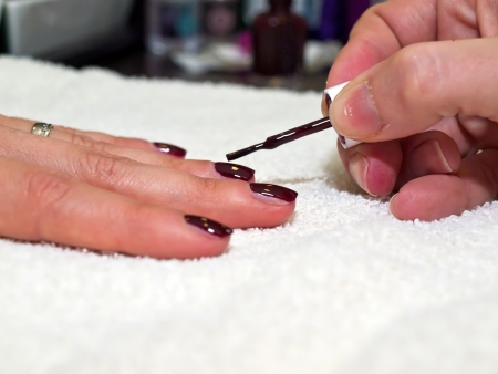Painting nails in red color on white towel