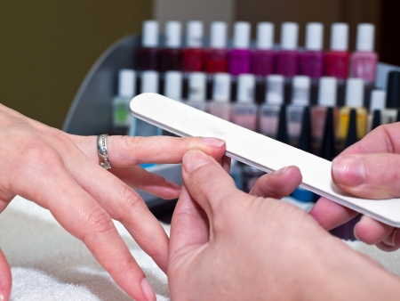 Woman nails manicure treatment in cosmetic salon Stock Photo