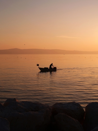 Fisherman with small boat in sunset on sea photo