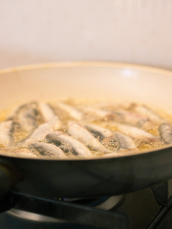 Frying fish in pan on olive oil Stock Photo