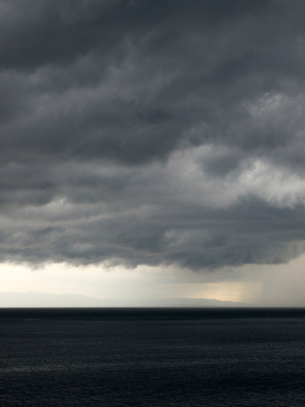 stormy clouds: Stormy clouds over sea with island in background