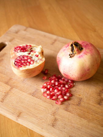 Pomegranates fruit on wooden board, shoot from above