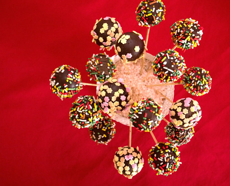 Chocolate cakepops on red background top view Stock Photo