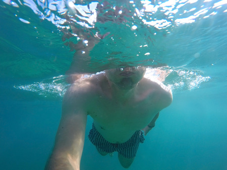 Young man making underwater selfie in clear sea
