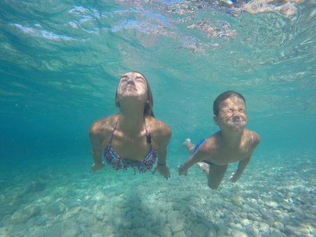 Mother and son diving underwater with funny face expression Stock Photo