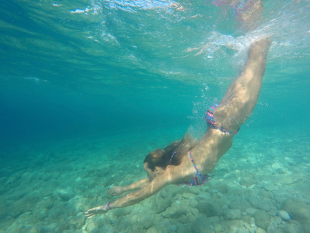 Young girl diving in crystal clear blue sea
