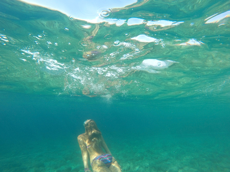 Young woman diving in blue sea underwater