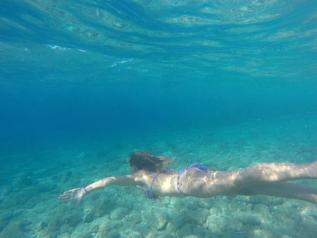 Young woman diving in crystal clear blue Adriatic sea Stock Photo