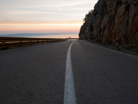 Asphalt mountain road above the sea at sunset
