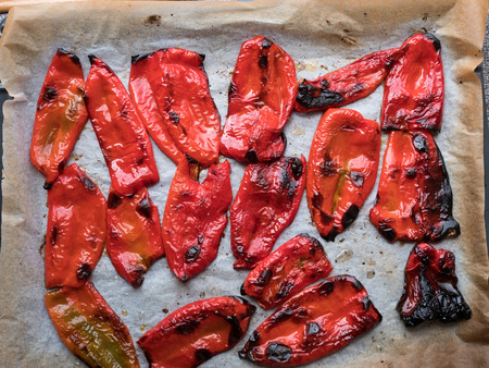 Grilled red shiny peppers on baking tray top view Stock Photo