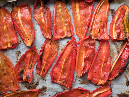 Roasted red peppers on baking paper top view Stock Photo