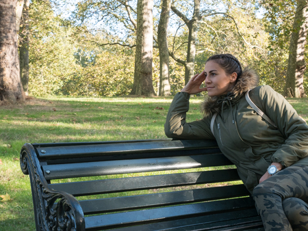 Young woman sitting alone on the bench in park Stock Photo