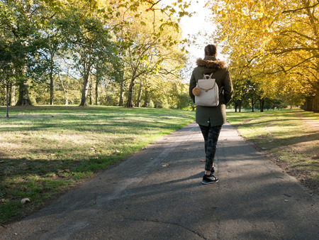 Young woman walking in the park at morning