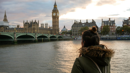 Woman near Thames river looking at Westminster