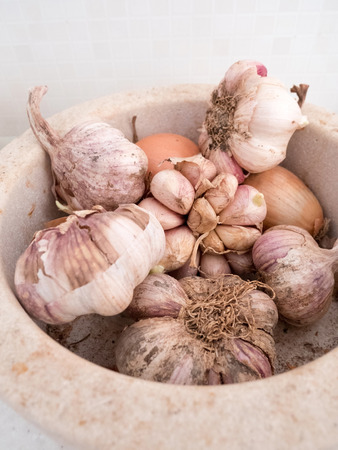 Garlic and onions in stone container in kitchen