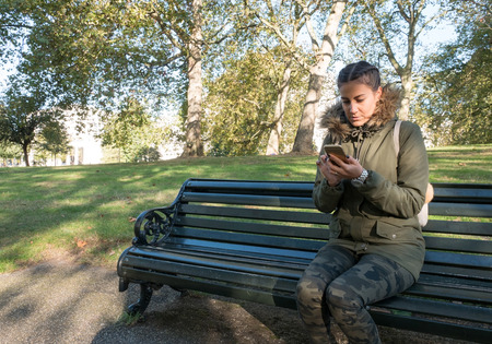 Young woman sitting on the bench in park and typing message on smart phone Stock Photo