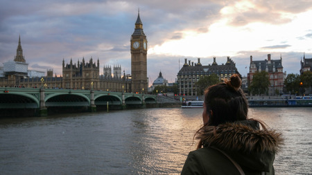 Woman looking at Westminster palace and Big Ben at sunset