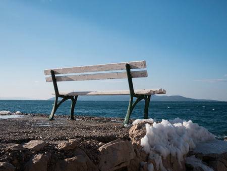 Empty bench on coastline at winter time with snow around