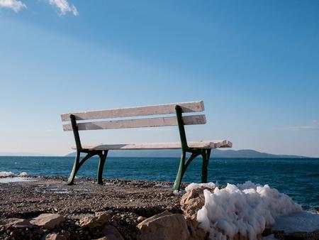 Frozen bench with snow around on Adriatic sea coast