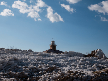 Lighthouse roof and coastline covered with snow on sunny day