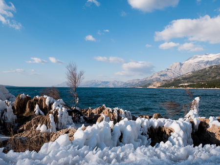Snow covered rocky coastline on sunny day at Adriatic sea coast