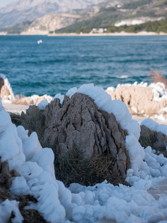 Snow covered rocky coastline on Adriatic sea coast