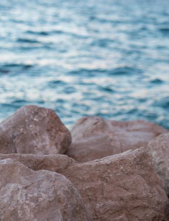 Stone coastline close up and blue sea background