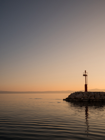Calm sea and red lighthouse tower on port entrance at sunset in Tucepi, Croatia Stock Photo