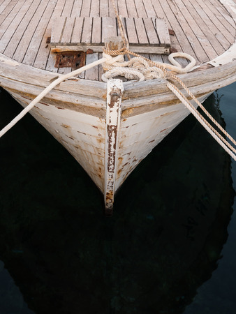 Front of rusty wooden boat in port