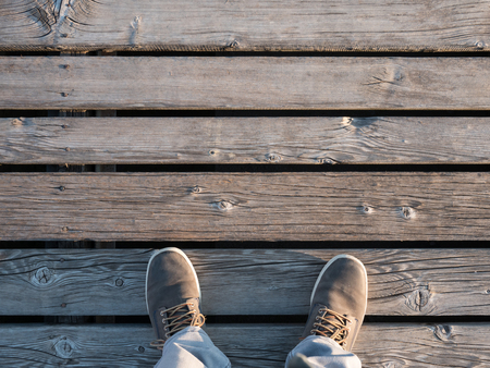 Man standing on the wooden pier top view Stock Photo