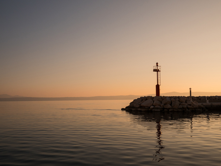 Red lighthouse tower on harbor entrance in Tucepi, Croatia