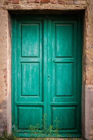 ghost town: Green door at Toiano, little ghost town in Tuscany, Italy Stock Photo