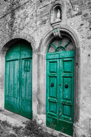 green door: Green door at Toiano, little ghost town in Tuscany, Italy Stock Photo