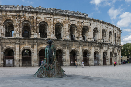 arles: Roman Arena (Amphitheater) in Arles and bullfighter sculpture, Provence, France Stock Photo