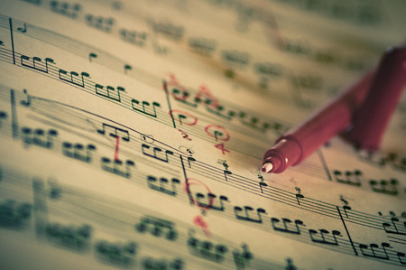 music notation: Close up of piano classic music score and notes and old paper with red pencil