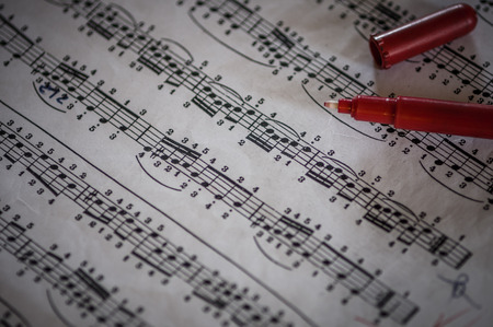 Close up of piano classic music score and notes and old paper with red pencil