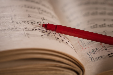 octaves: Close up of piano classic music score and notes and old paper with red pencil