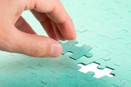 puzzle: Hand inserting missing piece of green jigsaw puzzle into the hole Stock Photo