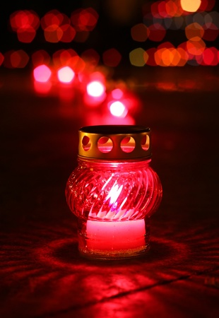 Closeup of red burning votive candle in lights background photo