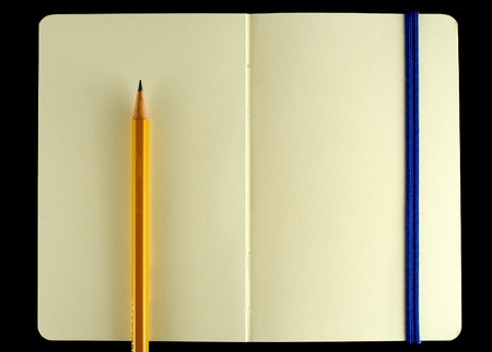 Classic opened moleskine note book with pencil isolated on black background photo