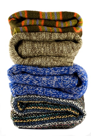 Pile of warm sweaters isolated on white photo