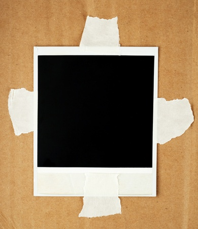 Blank photo card with masking tape on a cardboard photo